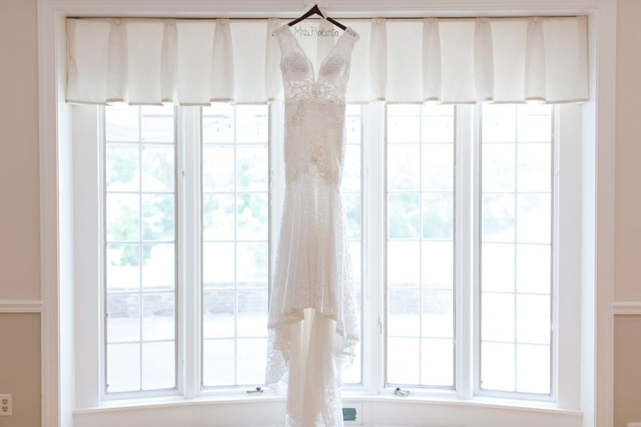 wide angle photo of the brides lace wedding gown by Calla Blanche hanging on a personalized wooden hanger in front of a large bay window