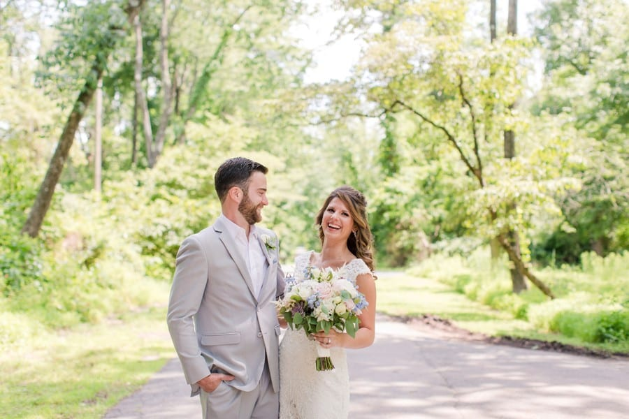 Groom laughing as he looks at his bride, also laughing (she is looking at the camera). She is holding her bridal bouquet by Monday Morning Flowers, consisting of various flowers of whites, pinks, ivories, with touches of lavendar and blue, with accompanying greenery