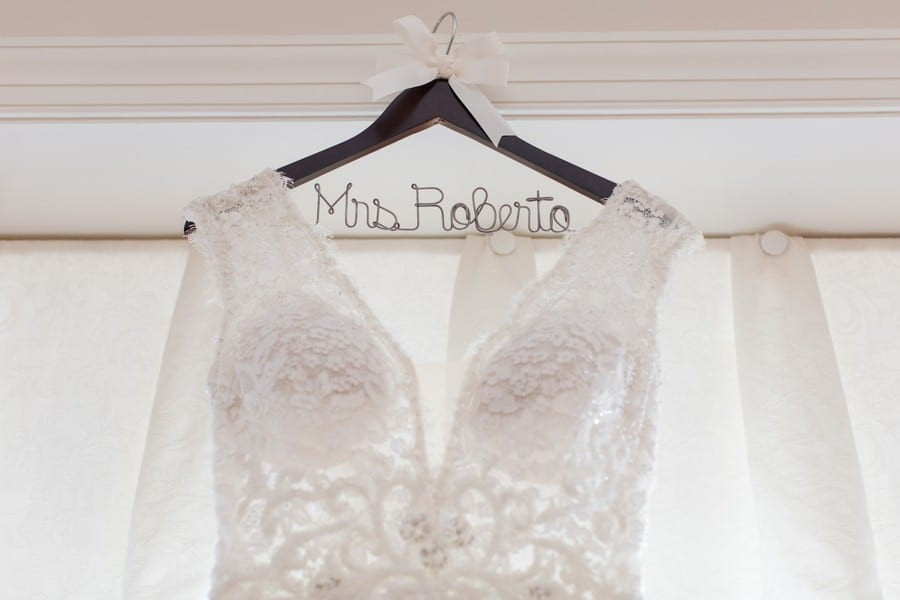 Close up photo of the brides lace gown hanging on a personalized dark wood hanger