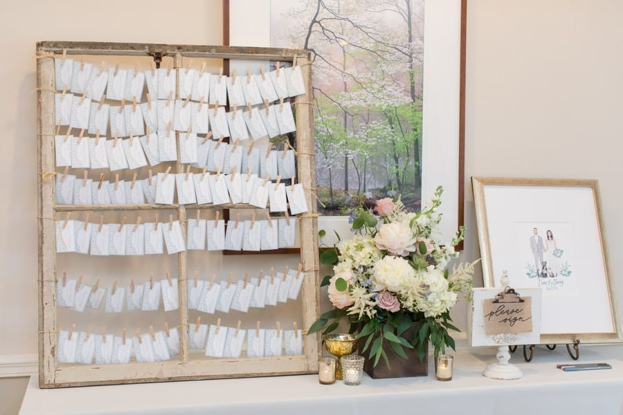 the place card holder of an old window pane with twine tied across it, each place card held to the twine with a mini clothespin. A guest sign in mat around a hand drawn picture of the bride and groom and their dog