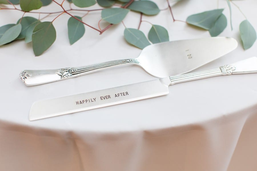 """Wedding details: the cake knife and server saying """"I do"""" and """"Happily Ever After"""""""