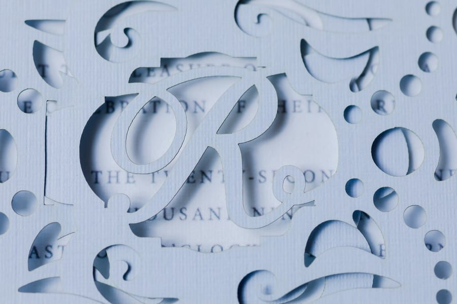 Close up of the personalized cut out R in light blue on the wedding invitation