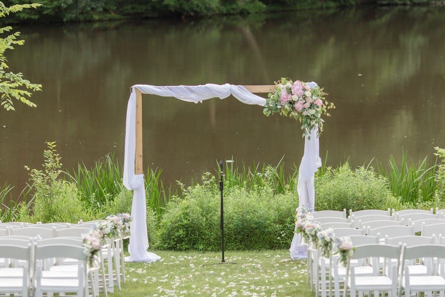 Wedding details: the ceremony location in front of the lake at the Mountain Lakes House in Princeton, NJ. The ceremony arch of wood, decorated in wrapped white chiffon, with a floral arrangement on the top left corner of pink and ivory florals and greens, with coordinating aisle decor