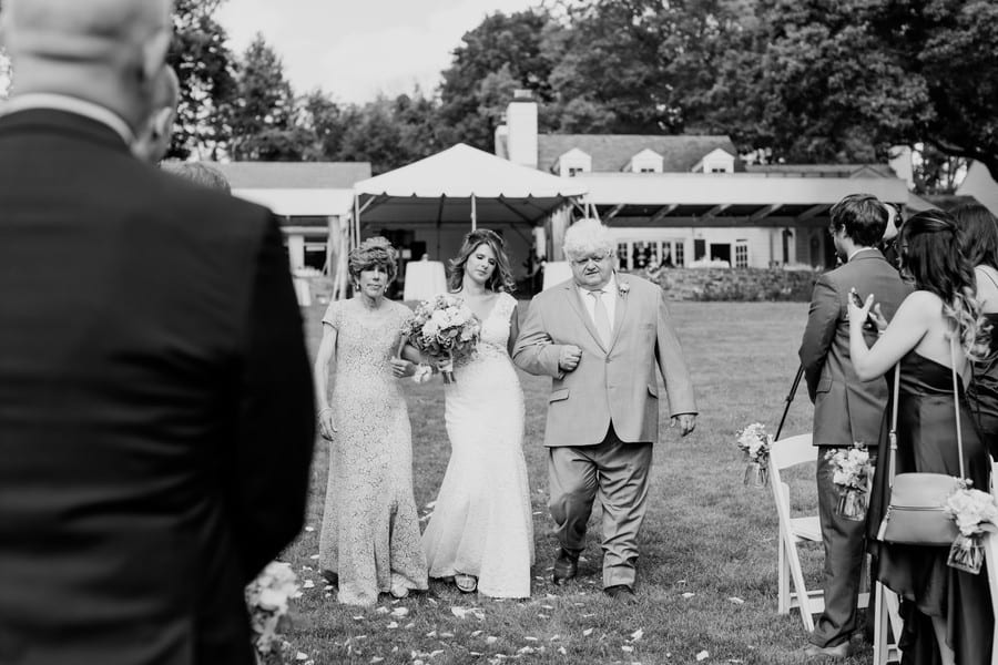 black and white photo of the bride being walked down the aisle by her mother and father