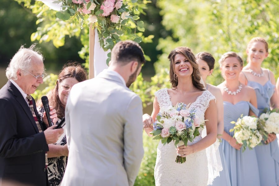 The bride laughs during the ceremony as the bridal party in dusty blue gowns by Azazie look on