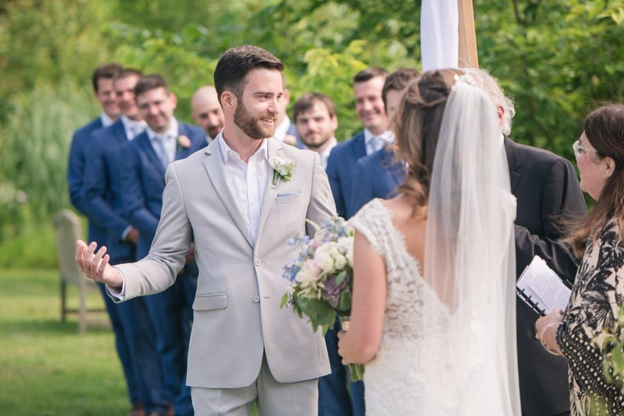 The groom in a gray suit by Generation Tux without a tie gestures during the wedding ceremony.
