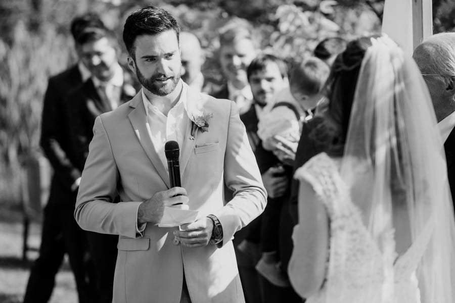Black and white photo of the groom making his vows to his bride