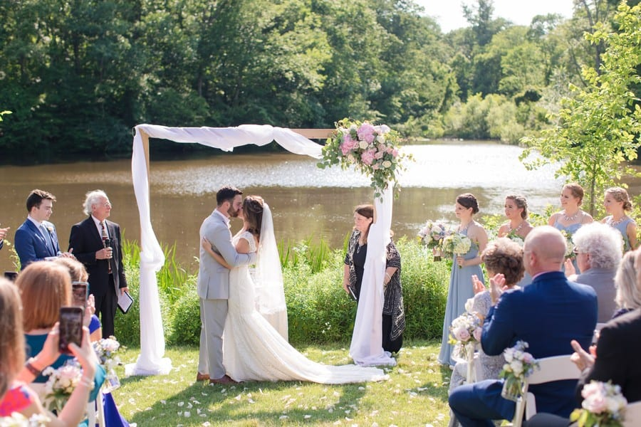 The newly married Mr and Mrs taking their first kiss as husband and wife under a white fabric wrapped wooden altar piece, decorated with pink florals with greenery at the top left corner in front of the lake at the Mountain Lakes House in Princeton, NJ