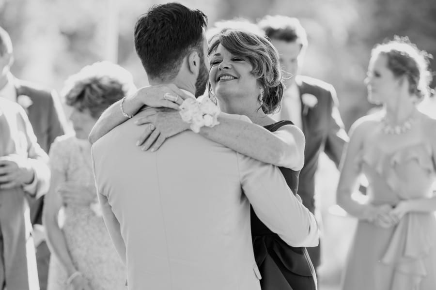 black and white photo of the mother of the groom smiling as she looks at him, arms wrapped around his neck for the mother of the groom dance