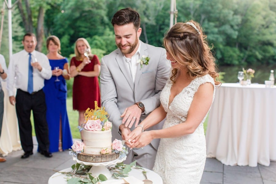 Bride and her groom cut the top tier of their wedding cake donut cake made by the Gingered Peach. The top tier is an off white frosted cake with dusty pink, blue and purple florals, with a gold cake topper, sitting on top a tree slab, sitting atop a white ruffled cake plate. Guests look on in the background, everyone is outdoors at the Mountain Lake House in Princeton, NJ
