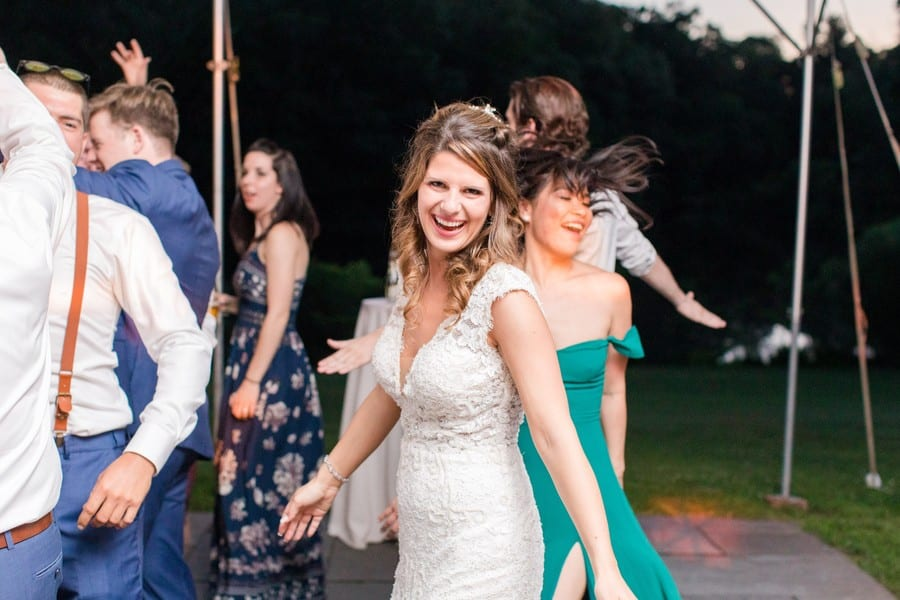 Candid photo of the bride laughing while dancing during the reception. Bride is wearing a white lace v-neck bridal gown by Calla Blanche