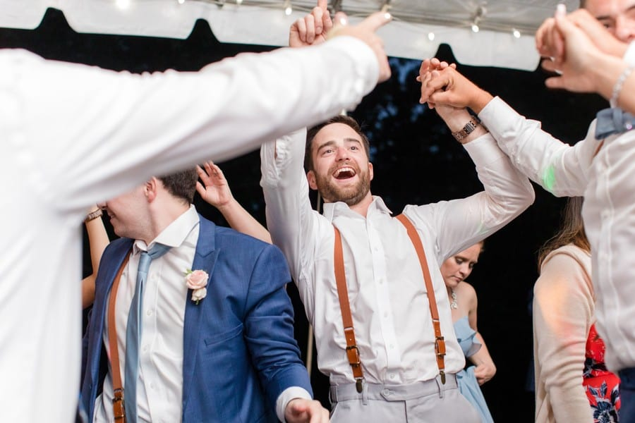 Candid photo of the groom laughing and dancing during the reception. Groom is wearing brown belt suspenders attached to suit pants by Generation Tux