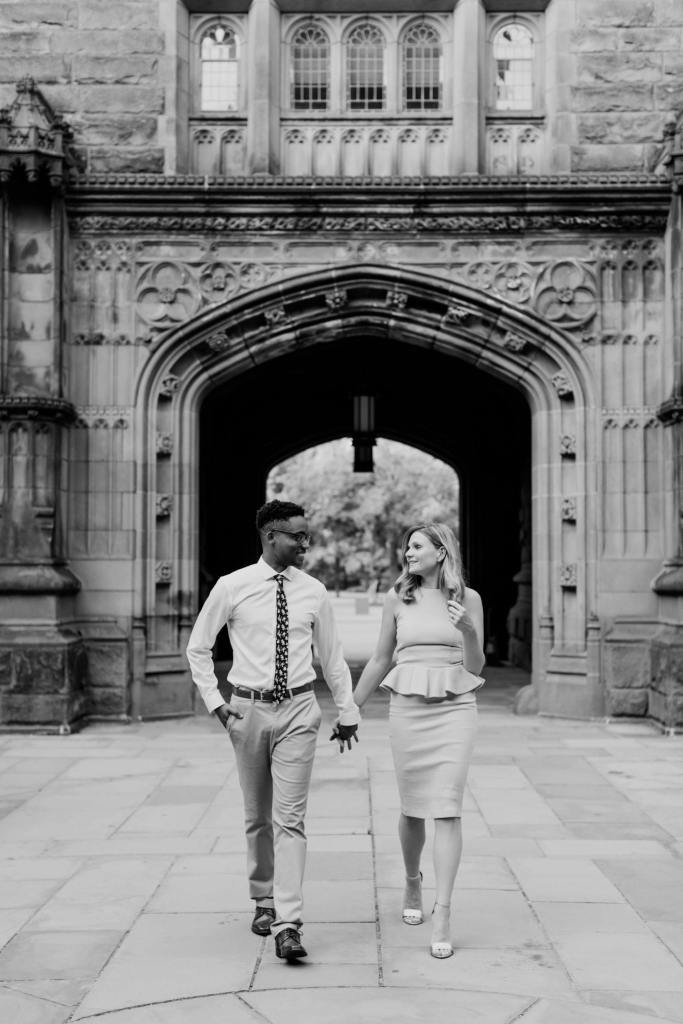 black and white photo of the engaged couple holding hands while walking, looking at one another, in front of Blair Hall on the campus of Princeton University