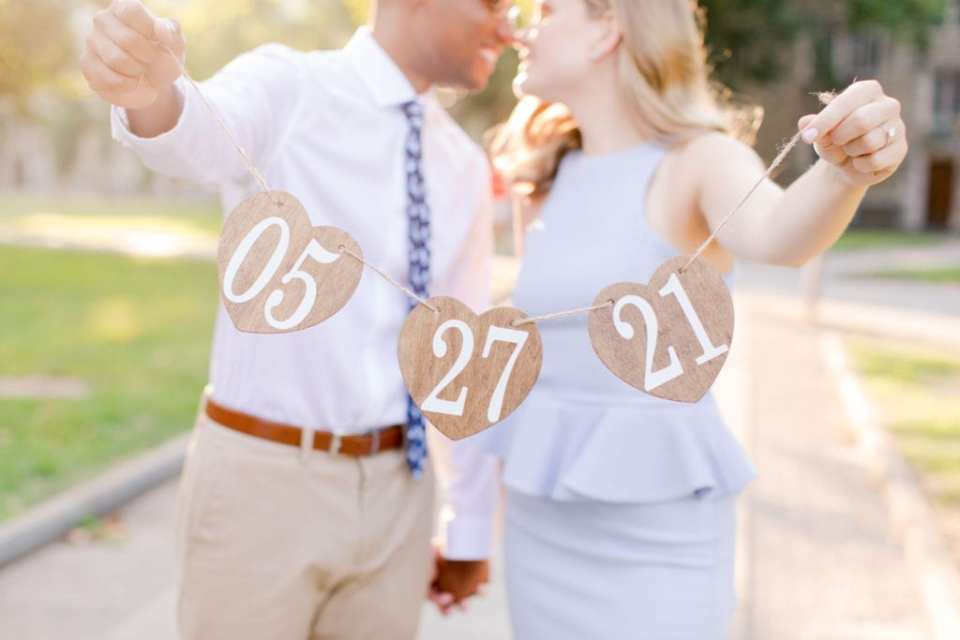 Engaged couple in background, holding hearts on twine with their wedding date in front of them, in focus, by Jaye Kogut Wedding Photography