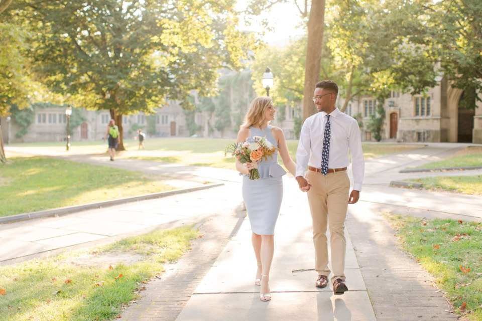 Bride and groom to be holding hands while walking around the campus of Princeton University, a floral bouquet of peaches, blues and whites by Magnolia West Events in her hand. Bride to be in a light blue sleeveless peplum dress from Castle Couture by John Paul Ataker, he in a shirt by Calvin Klein, tie by Bar III, pants by Old Navy.