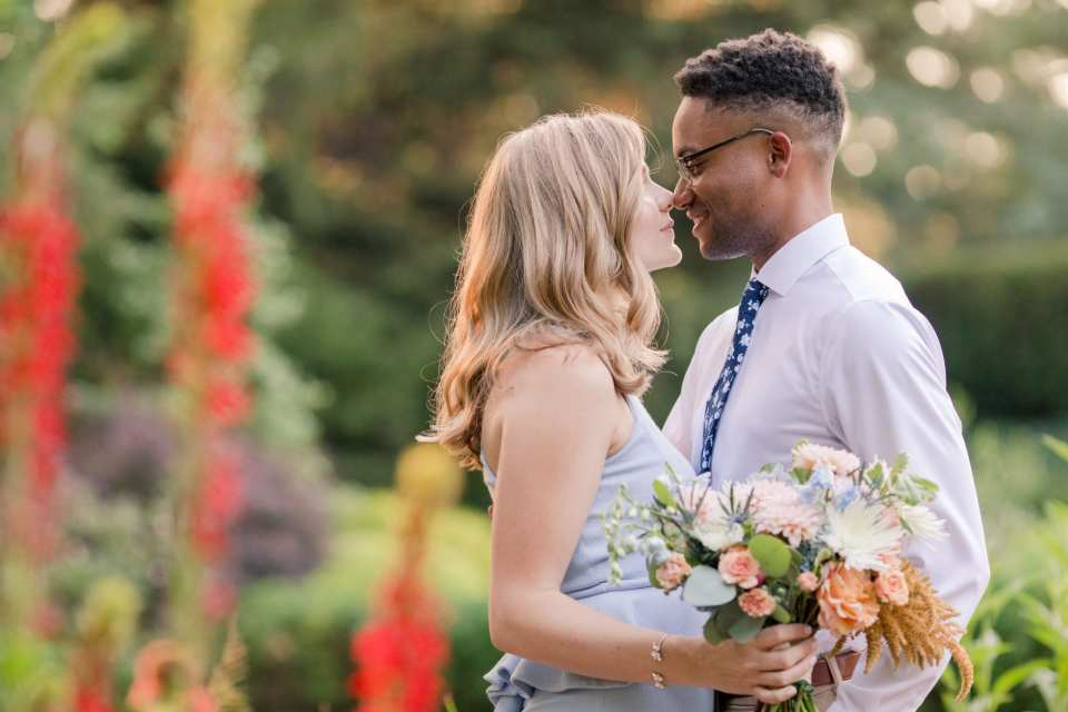 Bride and groom to be nose to nose in a garden, a floral bouquet of peaches, blues and whites by Magnolia West Events in her hand.