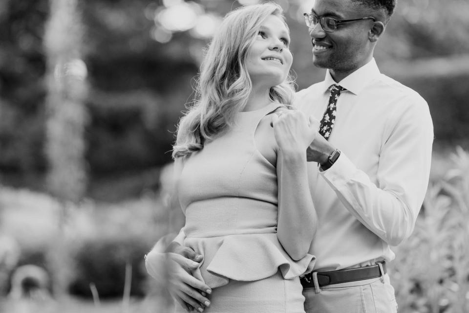 Black and white photo of engaged couple he standing behind her, she with her head looking back at him.