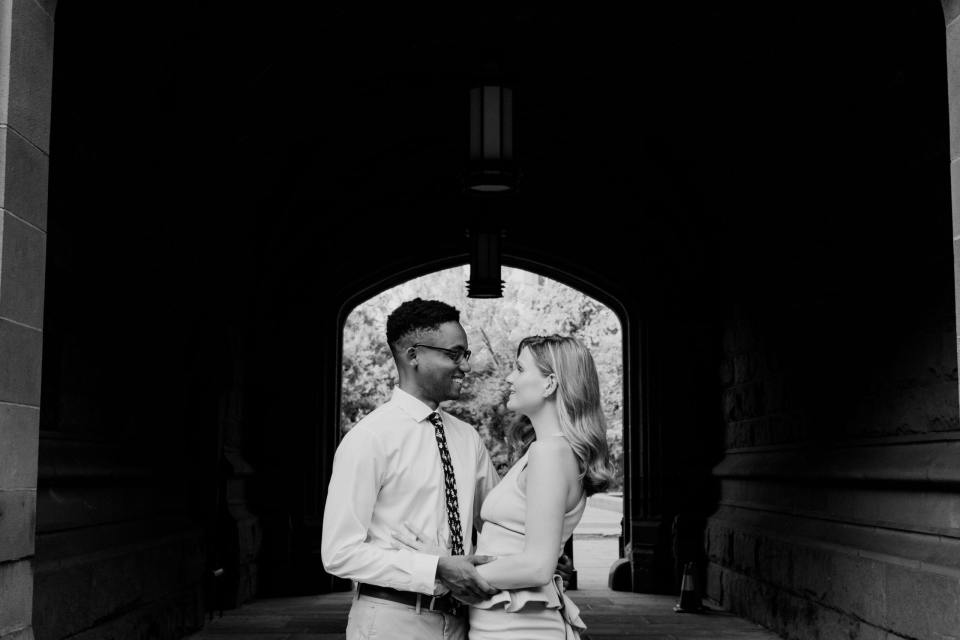 black and white photo of the engaged couple looking at one another in front of Blair Hall on the campus of Princeton University