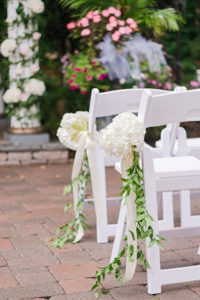 Wedding ceremony details: white hydrangeas and greens tied to white wooden folding chairs with white ribbon