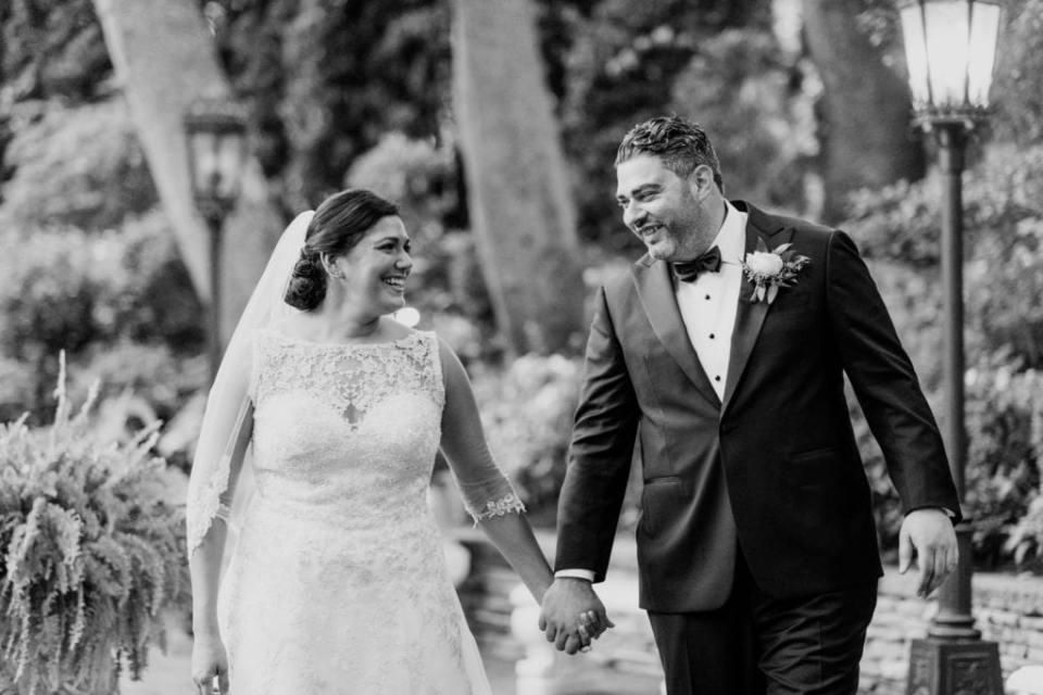 Black and white candid of the bride and groom walking, looking at one another smiling, while holding hands