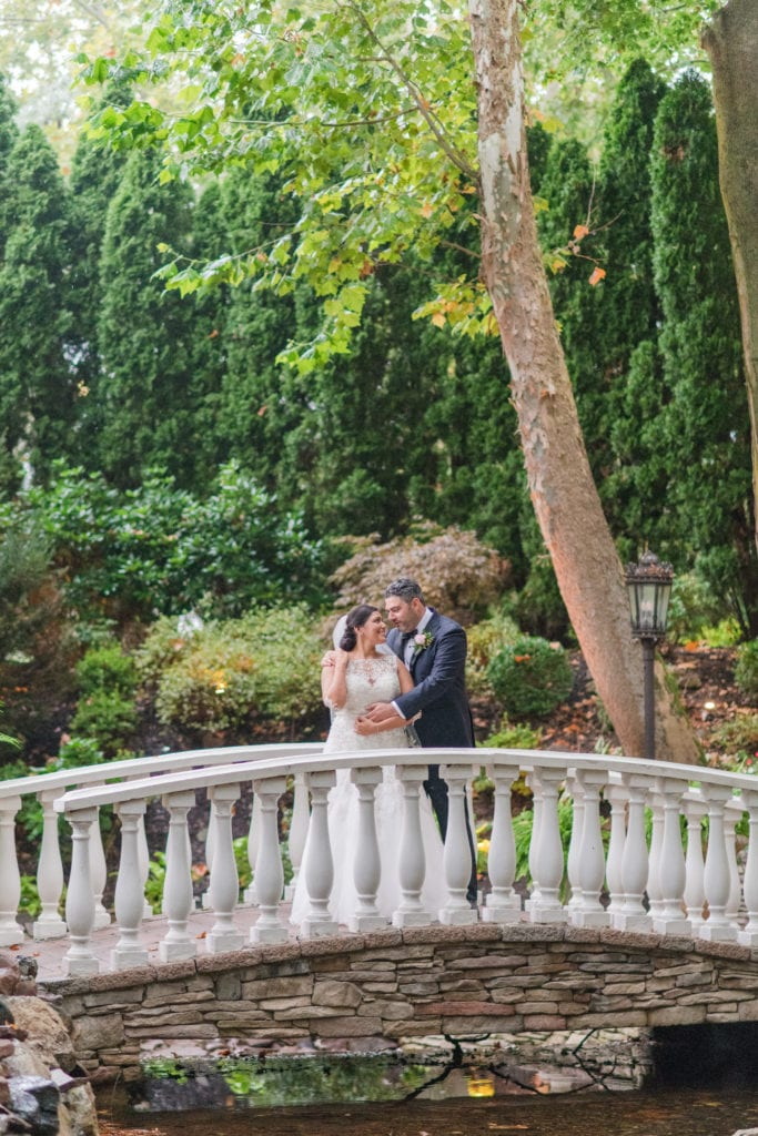 The bride being embraced from the side by her groom on the stone bridge at Nanina's in the Park