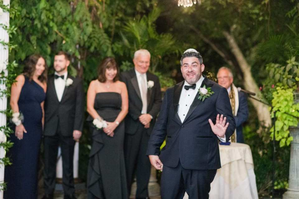 Candid photo of the groom waiting for his bride under the chuppah, with their families and wedding party in the background