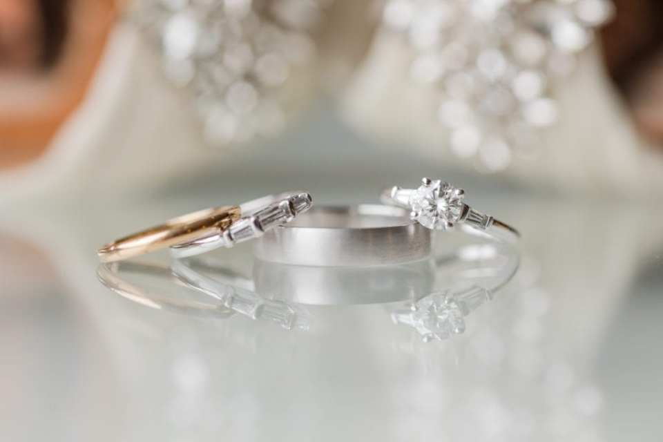 Brides round diamond solitaire engagement ring displayed with her coordinating wedding band, a gold wedding band, and her husbands brushed platinum wedding band by ES Nacht