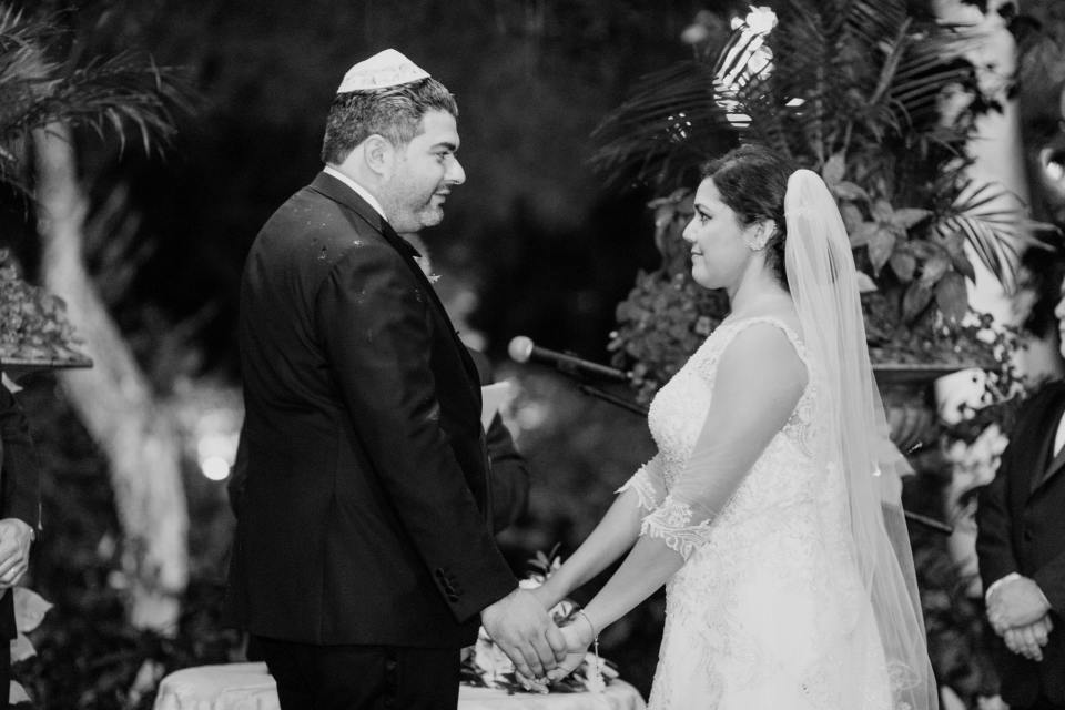 Black and white photo of the bride and groom holding hands, looking at one another, under the chuppah