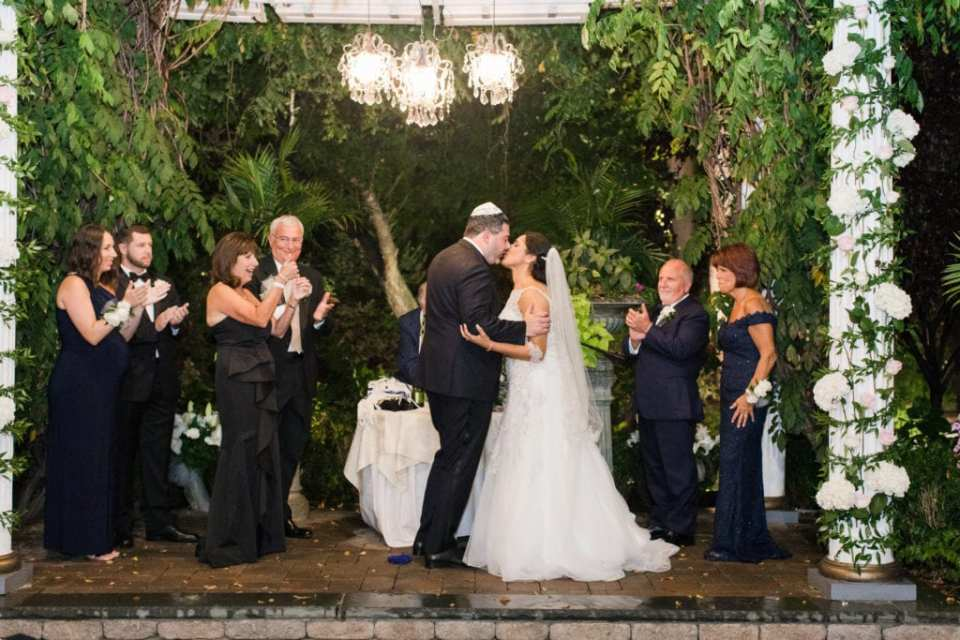 The bride and groom kiss under the chuppah at Nanina's in the Park for the first time as husband and wife as their families look on