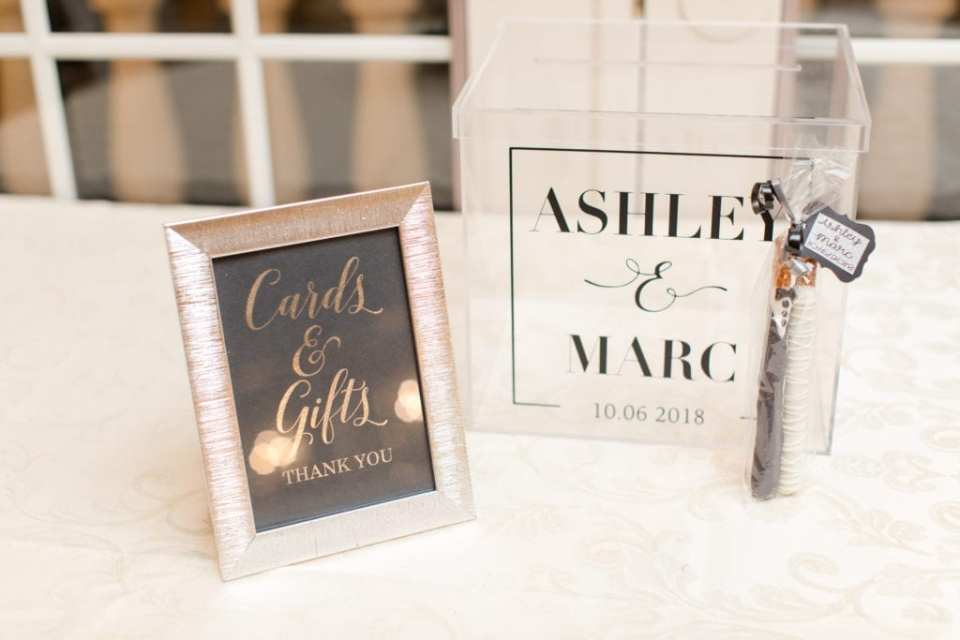 Wedding details: acrylic card box personalized with the bride and grooms name, with custom chocolate dipped pretzel favors leaning up against it