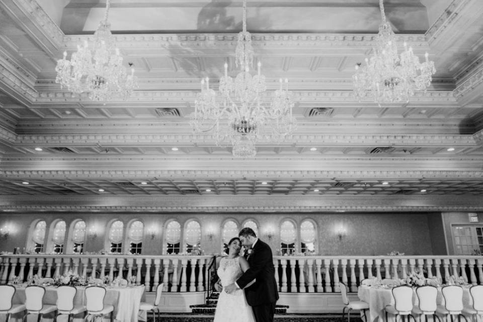 Black and white photo of the bride and groom in the center of the ballroom at Nanina's in the Park. He has his arms wrapped around her from behind
