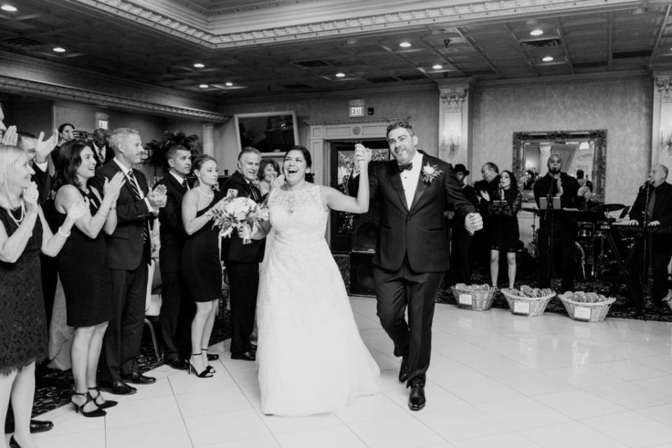 Black and white photo of the bride and groom making their grand entrance into the reception