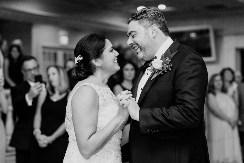 Black and white photo of the bride and groom smiling at each other during their first dance