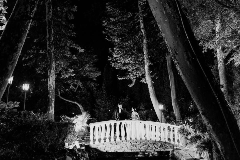Black and white photo of the bride and groom on the stone bridge outside of Nanina's in the Park at night