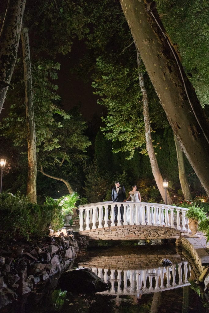 The bride and groom on the stone bridge outside of Nanina's in the Park at night