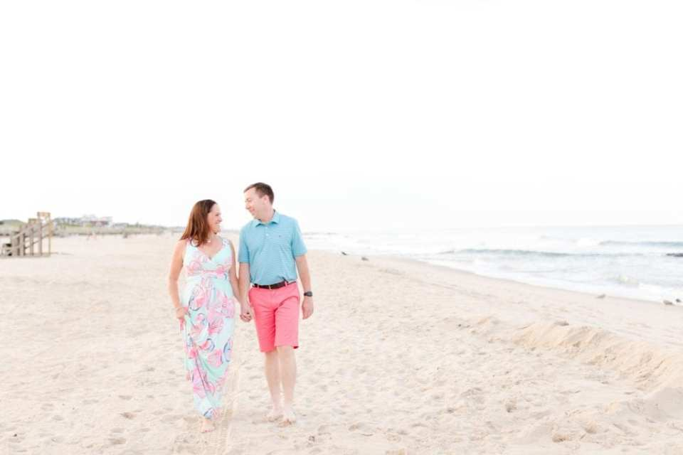 The future bride and groom walk on the beach in Spring Lake, New Jersey, holding hands and looking at one another. She is wearing Lilly Pulitzer, he is wearing Vineyard Vines