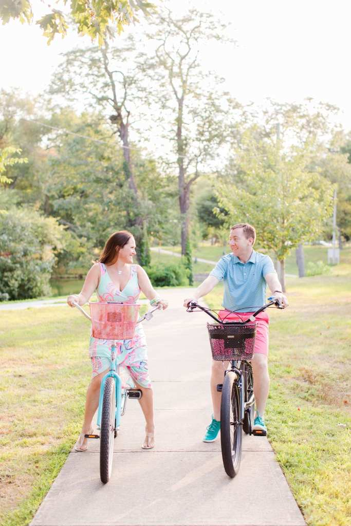 Bride and groom on antique bicycles in a park, looking at one another, smiling.