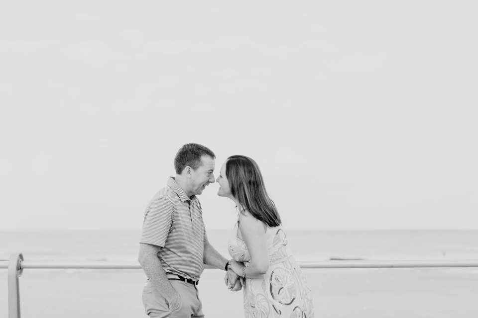 Black and white photo of the engaged couple on the boardwalk in Spring Lake, smiling ,nose to ose