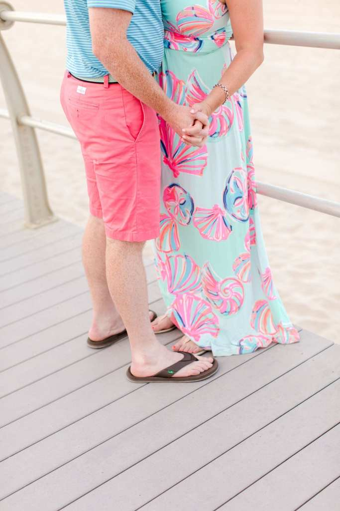 3/4 photo of engaged couple, focusing in on her hand in his. She is wearing Lilly Pulitzer, he is wearing Vineyard Vines.