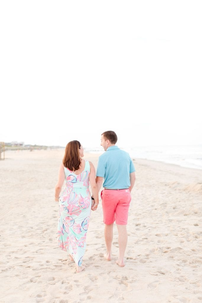 The future bride and groom walk on the beach in Spring Lake, New Jersey, holding hands and looking at one another (facing away from the camera). She is wearing Lilly Pulitzer, he is wearing Vineyard Vines