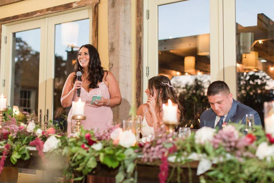 The maid of honor in a pink gown from Azazie stands next to the bride and groom while giving her speech
