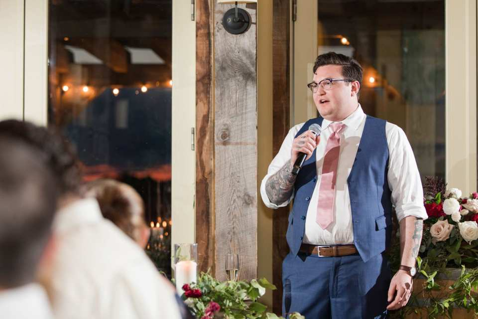 The best man in a navy blue tux and pink tie by Generation Tux gives his speech