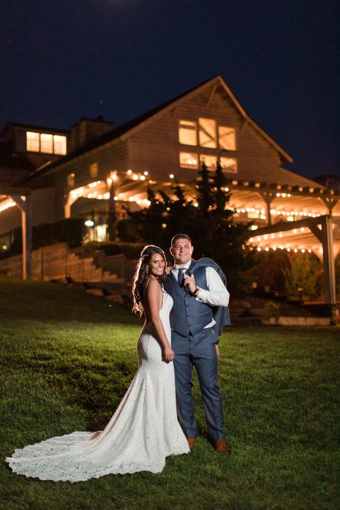 Bride in gown by Mikaella, standing next to groom in a tux from Generation Tux, both looking at the camera, grooms jacket over his shoulder, in front of a lit up Laurita Winery at night