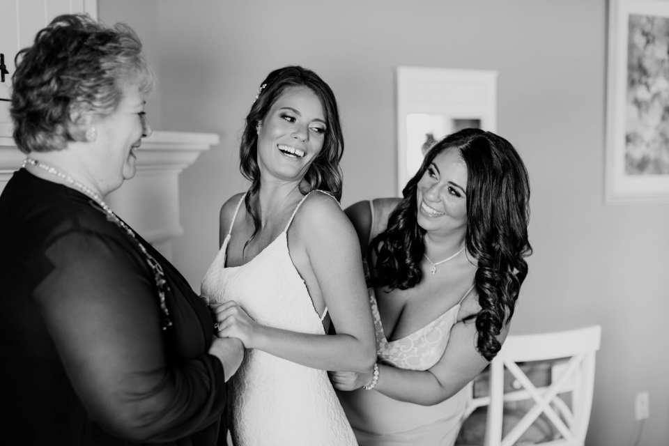 black and white candid of the bride, her mother and sister laughing while she is being helped into her gown
