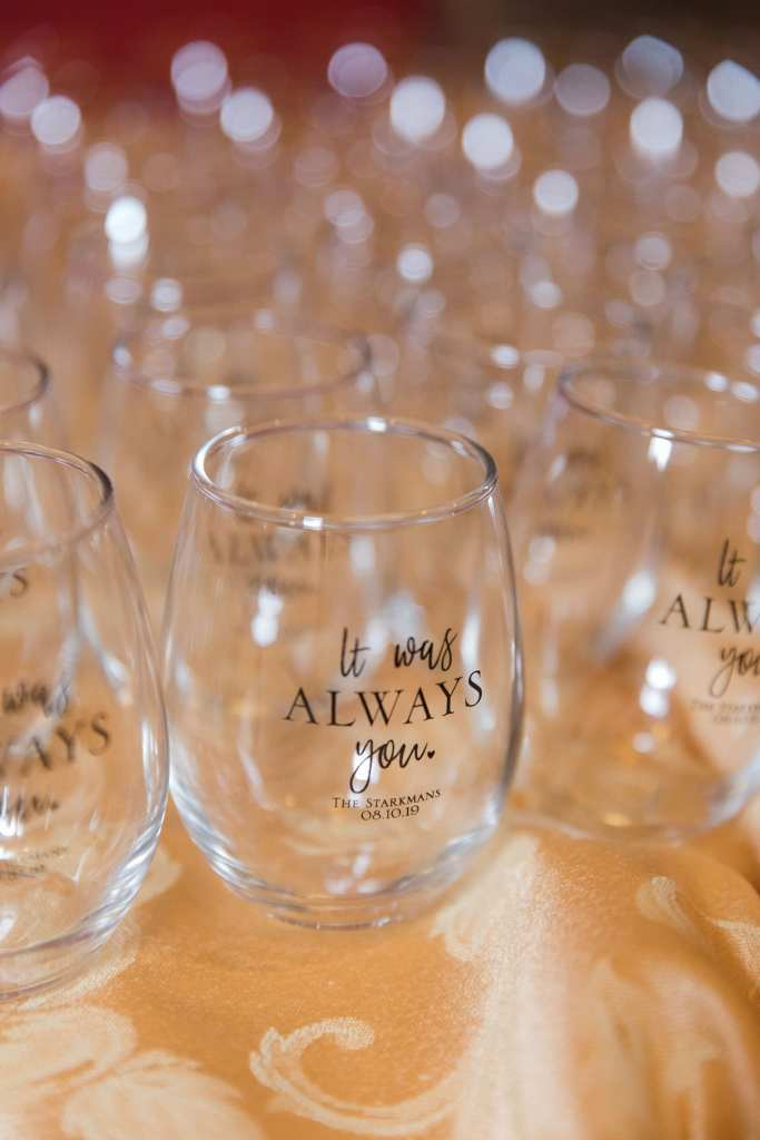 """Custom stemless wine glasses with the phrase """"It was always you"""" and the bride and groom's married name and date on display"""