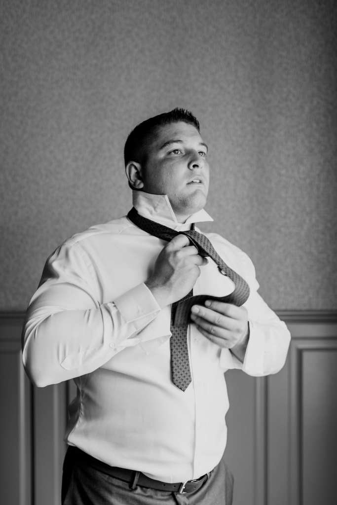 black and white candid photo of groom putting on his tie