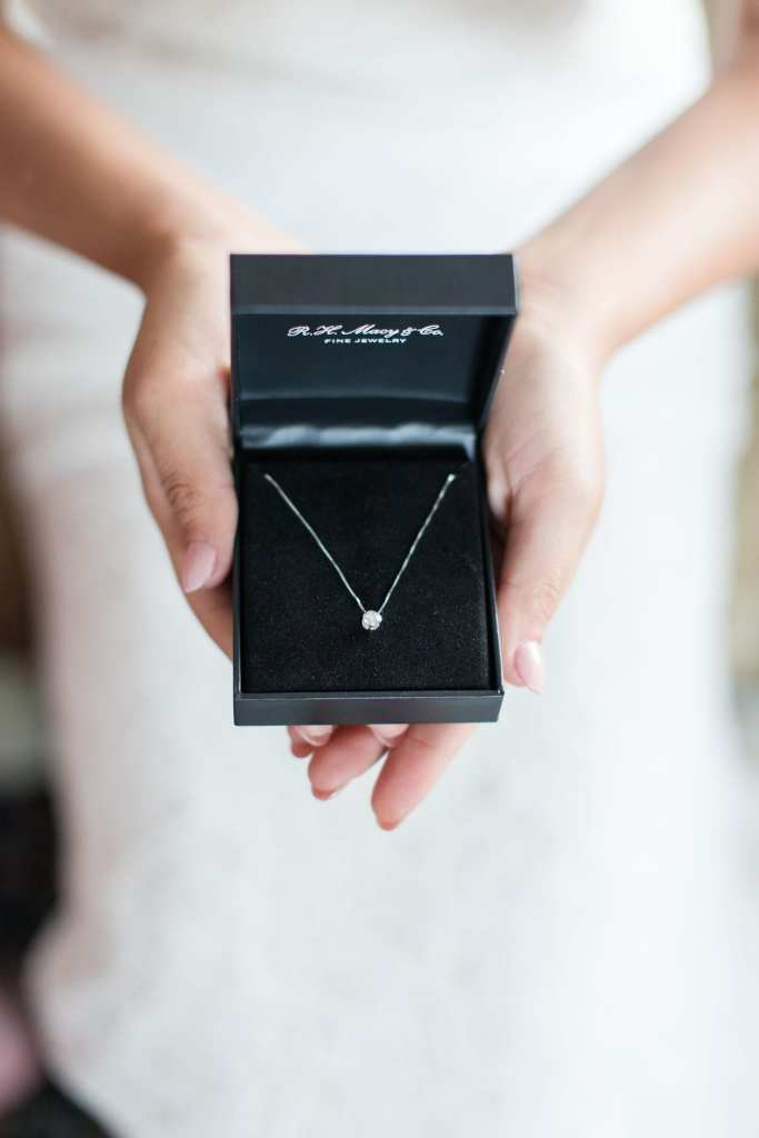 bride holding her diamond necklace from Macys in the palms of her hand