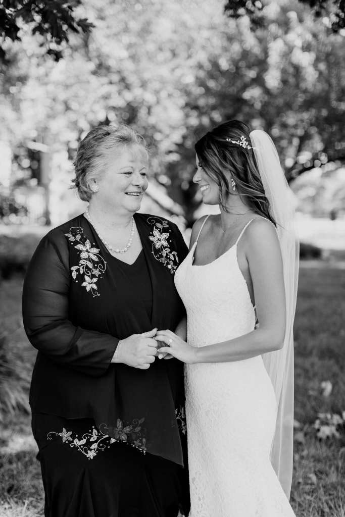 Black and white photo of the bride and her mother holding hands