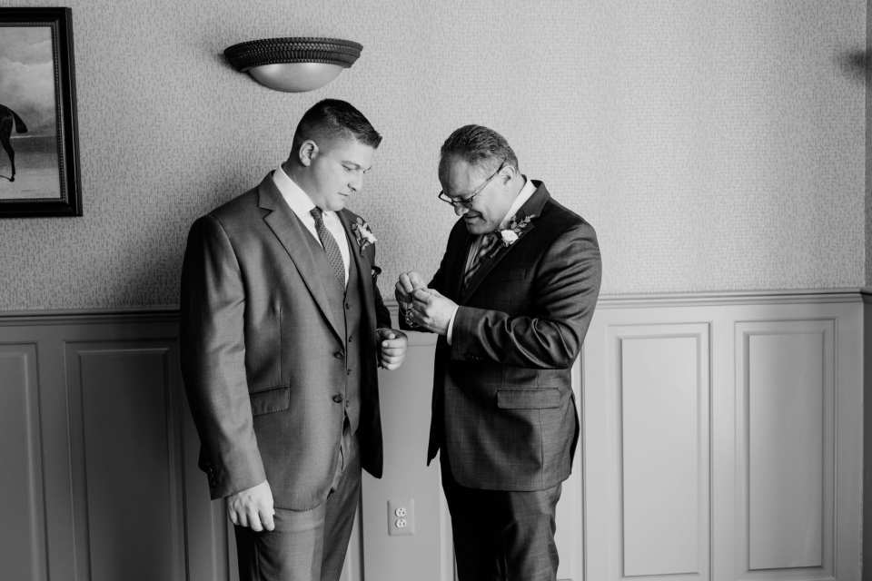 Black and white candid photo of the groom and his father