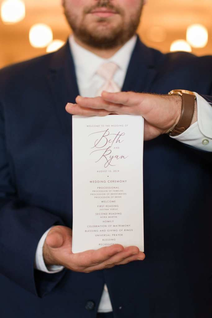 Close up photo of the ceremony program being held by a male family member